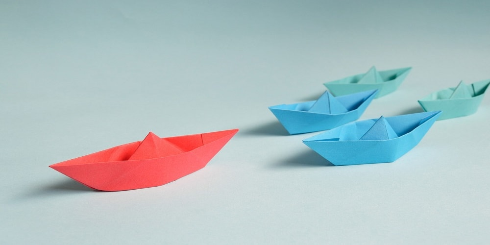 Red paper boat leading the pack to indicate Sitecore as a leader