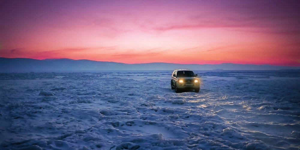 car driving in snow with sunset in background