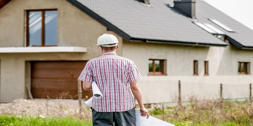 Man carrying architect plans in front of house